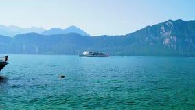Ένα σκάφος της γραμμής κρουαζιέρας με τα ελβετικά πανιά σημαιών κατά μήκος της λίμνης Λουκέρνη στα ξημερώματα απόθεμα βίντεο