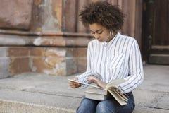 Ένα σκοτεινός-ξεφλουδισμένο κορίτσι κάθεται στα βήματα και κρατά μια ταμπλέτα και την εξετάζει Στα πόδια του είναι βιβλία στοκ φωτογραφίες