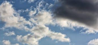 Ένα σκοτεινό μεγάλο σύννεφο και μικρά σγουρά σύννεφα Στοκ Εικόνα