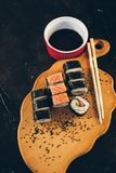 Ένα σούσι που τίθεται με τα ραβδιά κύπελλων και μπαμπού σάλτσας στο μαύρο υπόβαθρο στον ξύλινο πίνακα στοκ εικόνες