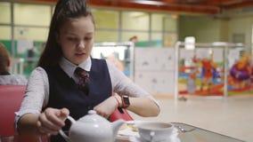 Ένα σπάσιμο στη σχολική καφετέρια Ένα έφηβη χύνει το τσάι από μια κατσαρόλα σε ένα φλυτζάνι απόθεμα βίντεο