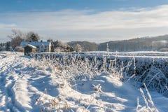 Ένα σπίτι και τομείς στο χιόνι Στοκ Φωτογραφίες