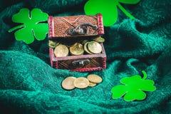 Ένα στήθος με τα χρυσά νομίσματα σε ένα πράσινο υπόβαθρο φύλλα τριφυλλιού Ημέρα StPatrick «s στοκ φωτογραφίες