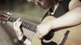 Ένα στενό επάνω πορτρέτο ενός κιθαρίστα που παίζει την χορδή-βασισμένη μελωδία απόθεμα βίντεο