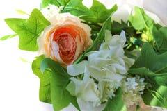 Ένα στεφάνι των άσπρων λουλουδιών και των πράσινων φύλλων σε ένα άσπρο υπόβαθρο στοκ εικόνες