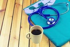 Ένα στηθοσκόπιο, ένα φλυτζάνι καφέ και ένας μπλε ιατρικός ομοιόμορφος σωρός σε ξύλινο Στοκ εικόνα με δικαίωμα ελεύθερης χρήσης