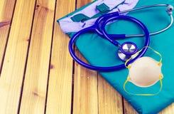 Ένα στηθοσκόπιο, μια μάσκα και ένας μπλε ιατρικός ομοιόμορφος σωρός σε ξύλινο Στοκ εικόνα με δικαίωμα ελεύθερης χρήσης
