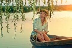 Ένα στοχαστικό κορίτσι σε μια βάρκα στο ηλιοβασίλεμα Στοκ εικόνα με δικαίωμα ελεύθερης χρήσης