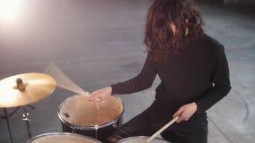 Ένα συγκρότημα ροκ που έχει μια επανάληψη Ένα άτομο με το δροσερό μακρυμάλλες παιχνίδι παίζει τύμπανο απόθεμα βίντεο