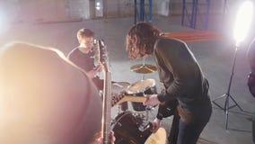 Ένα συγκρότημα ροκ προοπτικής που έχει μια επανάληψη Νέοι στα μαύρα ενδύματα που παίζουν τους ρόούς τους απόθεμα βίντεο