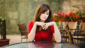 Ένα συμπαθητικό κορίτσι κάθεται σε έναν καφέ Στοκ Εικόνες