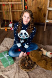 Ένα συμπαθητικό κορίτσι κάθεται σε ένα δωμάτιο με τους ξύλινους τοίχους Νέο έτος και Chris Στοκ Φωτογραφία