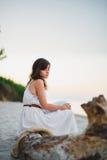 Ένα συμπαθητικό κορίτσι κάθεται στην ακροθαλασσιά Στοκ Εικόνες