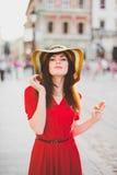 Ένα συμπαθητικό κορίτσι σε ένα κόκκινο φόρεμα στο πόλη-κέντρο Στοκ Εικόνες