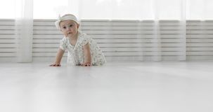 Ένα συμπαθητικό μικρό κορίτσι σε έναν επίδεσμο και ένα φόρεμα που σέρνονται στο άσπρο πάτωμα φιλμ μικρού μήκους