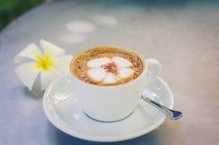 Ένα σχέδιο plumeria φλιτζανιών του καφέ σε ένα άσπρο φλυτζάνι στο ξύλινο υπόβαθρο Στοκ φωτογραφίες με δικαίωμα ελεύθερης χρήσης