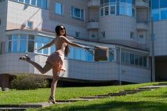 Ένα σύγχρονο κορίτσι σε ένα φόρεμα, τα γυαλιά και μια τσάντα πηδά στην πορεία Συγκίνηση της ευτυχίας και της επιτυχίας νεολαίες ε Στοκ Εικόνα