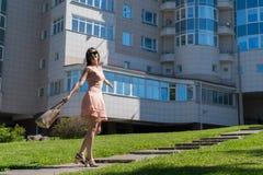 Ένα σύγχρονο κορίτσι σε ένα φόρεμα, τα γυαλιά και μια τσάντα που στην πορεία Συγκίνηση της ευτυχίας και της επιτυχίας νεολαίες επ Στοκ φωτογραφία με δικαίωμα ελεύθερης χρήσης