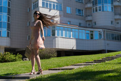 Ένα σύγχρονο κορίτσι σε ένα φόρεμα, τα γυαλιά και μια τσάντα που στην πορεία Συγκίνηση της ευτυχίας και της επιτυχίας νεολαίες επ Στοκ Φωτογραφίες