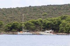 Ένα σύγχρονο πλέοντας γιοτ δένεται σε έναν κόλπο Οι άνθρωποι λούζουν στη θάλασσα Ενεργό υπόλοιπο στην αδριατική θάλασσα της περιο στοκ εικόνες