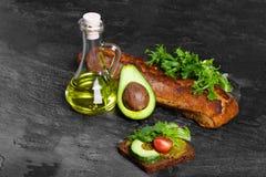 Ένα σύνολο βάζων γυαλιού ενός ελαίου αβοκάντο και ενός πρόσφατα ψημένου ψωμιού σε ένα σκούρο γκρι υπόβαθρο Θρεπτικά και υγιή πρόχ Στοκ Εικόνα