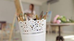 Ένα σύνολο βουρτσών για τη ζωγραφική σε ένα πλαστικό φλυτζάνι φιλμ μικρού μήκους