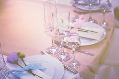 Ένα σύνολο γυαλιού του γάμου που θέτει με τα μαχαιροπήρουνα με ένα ιώδες λουλούδι αυξήθηκε Πίνακας για ένα κόμμα ή μια δεξίωση γά στοκ φωτογραφία με δικαίωμα ελεύθερης χρήσης