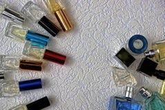 Ένα σύνολο γυαλιού χρωμάτισε τα μπουκάλια με το άρωμα σε μια γκρίζα επιφάνεια Στοκ Εικόνα