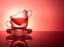Ένα σύνολο δύο φλυτζανιών γυαλιού για το τσάι σε ένα κόκκινο ρόδινο υπόβαθρο στοκ φωτογραφίες
