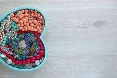 Ένα σύνολο κοσμήματος για τις γυναίκες σε έναν ξύλινο δίσκο με μορφή μιας καρδιάς Στοκ Εικόνες
