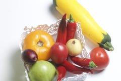 Ένα σύνολο λαχανικών για τη σαλάτα βρίσκεται σε ένα καλάθι δαντελλών Σε μια άσπρη ανασκόπηση Κρεμμύδια και ντομάτες των διαφορετι Στοκ Εικόνες