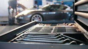 Ένα σύνολο εργαλείων για την επισκευή στην υπηρεσία αυτοκινήτων μπροστά από το σπορ αυτοκίνητο πολυτέλειας - πυροβολισμός ολισθαι απόθεμα βίντεο