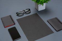 Ένα σύνολο μαύρων εξαρτημάτων γραφείων, γυαλιά, πράσινο λουλούδι και έξυπνος στο γκρίζο υπόβαθρο Στοκ Φωτογραφίες