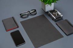 Ένα σύνολο μαύρων εξαρτημάτων γραφείων, γυαλιά, πράσινο λουλούδι και έξυπνος στο γκρίζο υπόβαθρο Στοκ Φωτογραφία