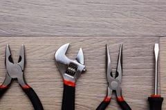 Ένα σύνολο με το εργαλείο σε έναν ξύλινο πίνακα Σφυρί, κατσαβίδι, gayachnye γαλλικά κλειδιά, πένσες, κόπτες καλωδίων Τοπ όψη Στοκ Φωτογραφία