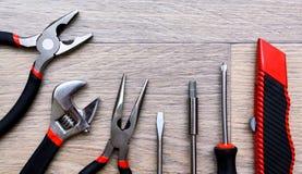 Ένα σύνολο με το εργαλείο σε έναν ξύλινο πίνακα Σφυρί, κατσαβίδι, gayachnye γαλλικά κλειδιά, πένσες, κόπτες καλωδίων Τοπ όψη Στοκ Εικόνες