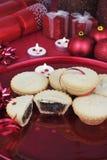 Ένα σύνολο πιάτων των Χριστουγέννων κομματιάζει τις πίτες με τις κόκκινες διακοσμήσεις Στοκ Εικόνες
