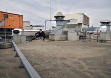 ένα τέντωμα νεαρών άνδρων υπαίθρια στη στέγη Στοκ Εικόνες