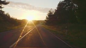 Ένα ταξίδι σε έναν αγροτικό δρόμο στο ηλιοβασίλεμα απόθεμα βίντεο