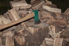 Ένα τεμαχίζοντας δέντρο τσεκουριών είναι κολλημένο σε ένα κολόβωμα Στοκ Εικόνες