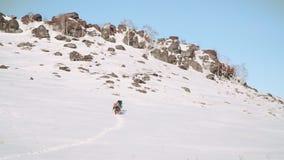 Ένα τεράστιο βουνό κάλυψε με το χιόνι και εξέθεσε τους βράχους, αυξάνεται μια μεγάλη ομάδα των ορειβατών που κρεμιούνται με τον ε απόθεμα βίντεο