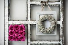 Ένα τετράγωνο των λουλουδιών σε ένα πλαίσιο παραθύρων στοκ φωτογραφία
