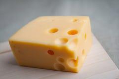 Ένα τετραγωνικό κομμάτι του τυριού maasdam με τις τρύπες εξυπηρέτησε στο αγροτικό ύφος σε έναν ξύλινο πίνακα κλείστε επάνω Τρόφιμ Στοκ φωτογραφία με δικαίωμα ελεύθερης χρήσης