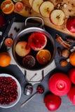 Ένα τηγάνι με ένα ευώδες θερμαμένο κρασί, επόμενες φέτες των juicy μήλων, ένα πιάτο με τα τα βακκίνια και τα κεριά επάνω από την  Στοκ φωτογραφία με δικαίωμα ελεύθερης χρήσης
