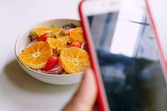 ένα τηλέφωνο, που κλείνει μια οθόνη, τοποθετημένος στο πρώτο πλάνο, υγιή γεύματα, Α ανάμιξε τη σαλάτα στοκ εικόνες με δικαίωμα ελεύθερης χρήσης