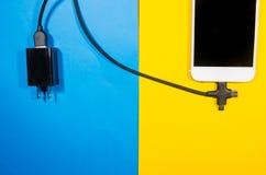 Ένα τηλέφωνο χρέωσης σύνδεσε με το φραγμό προσαρμοστών μέσω του μαύρου καλωδίου στοκ εικόνα