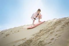 Ένα τολμηρό μικρό κορίτσι που επιβιβάζεται κάτω από τους αμμόλοφους άμμου στοκ εικόνες