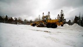 Ένα τρακτέρ καθαρίζει το χιόνι από το έδαφος για το καθαρίζοντας χιόνι αυτοκινήτων από τη μεγάλη τεχνική δεικτών φιλμ μικρού μήκους