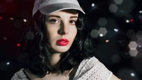 Ένα τρομερό νέο brunette σε μια γκρίζα ΚΑΠ Στοκ Εικόνες