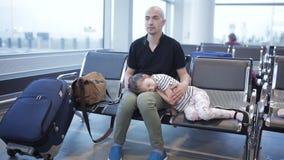 Ένα τρυπημένο άτομο στον αερολιμένα γαιδάρων που περιμένει με μια μικρή κουρασμένη κόρη στα όπλα της που περιμένει την έναρξη της απόθεμα βίντεο